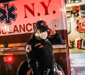FDNY paramedic Elizabeth Bonilla center wipes a tear from her eye while wearing personal protective equipment due to COVID-19 concerns after an emergency call, Wednesday, April 15, 2020, in the Bronx borough of New York.