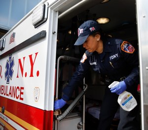 FDNY paramedic Elizabeth Bonilla strictly disinfects her ambulance prior to a double shift at EMS Station 3, Wednesday, April 15, 2020, in the Bronx borough of New York. (AP Photo/John Minchillo)