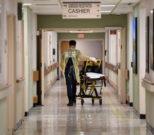 A Prince George County firefighter walks the halls of UM Laurel Medical Center in Laurel, Md., Friday, April 17, 2020. (AP Photo/Susan Walsh)