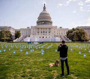 A man stops to take a photograph as he walks his dog past a thousand signs made by the advocacy group MoveOn along with other organizations that read #GetUsPPE, on the West Lawn of the U.S. Capitol, Friday, April 17, 2020, in Washington. U.S. Rep. Matt Cartwright has unveiled a proposal to provide hazard pay to front-line workers, including first responders and healthcare professionals, during the COVID-19 pandemic. (AP Photo/Andrew Harnik)