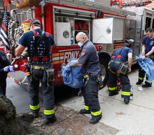 FDNY personnel disrobe from their protective equipment after an emergency call at Cobble Hill Health Center, Friday, April 17, 2020, in the Brooklyn borough of New York. New York City Mayor Bill de Blasio has announced that health insurance for families of city workers who died from COVID-19, including first responders, will be extended for 45 days. (AP Photo/John Minchillo)