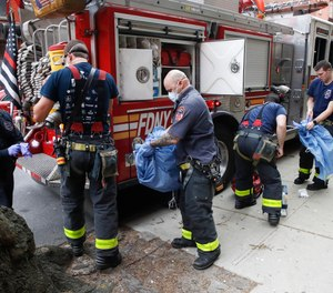 FDNY personnel disrobe from their protective equipment after an emergency call at Cobble Hill Health Center, Friday, April 17, 2020, in the Brooklyn borough of New York. New York City Mayor Bill de Blasio has announced that health insurance for families of city workers who died from COVID-19, including first responders, will be extended for 45 days.