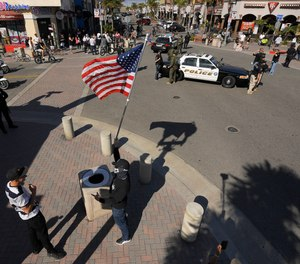 A protester, center foreground, stands with a flag as police block off an intersection during a demonstration against stay-at-home orders that were put in place due to the COVID-19 outbreak, Friday, April 17, 2020, in Huntington Beach, Calif.