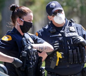In Tuesday, April 21, 2020, photo, Salt Lake City police officers wear face masks to protect against the spread of the new coronavirus as they patrol in Salt Lake City. (AP Photo/Rick Bowmer)