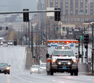 A ambulance on a call drives on Commonwealth, Ave., Friday, April 24, 2020, in Boston. (AP Photo/Michael Dwyer)