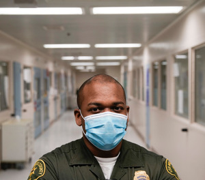 In this April 16, 2020, photo Christopher Lumpkin, a custody assistant, poses for a picture at the hospital ward of the Twin Towers jail in Los Angeles.