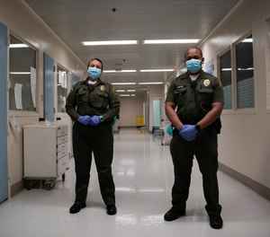 In this April 16, 2020, photo Sonia Munoz, left, and Christopher Lumpkin, custody assistants, poses for a picture at the hospital ward of the Twin Towers jail in Los Angeles.