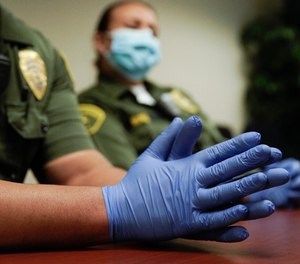 In this April 16, 2020, photo Christopher Lumpkin's gloved hands are shown during an interview at the hospital ward of the Twin Towers jail in Los Angeles. Across the country first responders who've fallen ill from COVID-19, recovered have begun the harrowing experience of returning to jobs that put them back on the front lines of America's fight against the novel coronavirus.