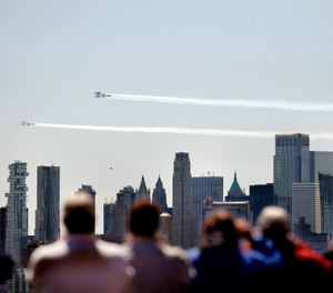 People watch as a formation of the Blue Angels and Thunderbirds flight teams pass in front of the New York City skyline as seen from in Weehawken, N.J., Tuesday, April 28, 2020. The flyover was in salute to first responders in the fight against the new coronavirus. (AP Photo/Seth Wenig)