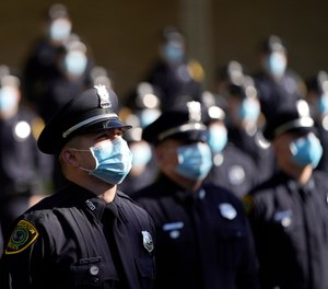 Houston Police cadets wear masks amid the COVID-19 pandemic while taking a class photo during a graduation ceremony at the Houston Police Academy, Friday, May 1, 2020, in Houston. (AP Photo/David J. Phillip)