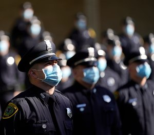Houston Police cadets wear masks amid the COVID-19 pandemic while taking a class photo during a graduation ceremony at the Houston Police Academy, Friday, May 1, 2020, in Houston.