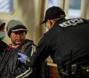 A New York Police officer attempts to help a man on the Coney Island Stillwell Avenue subway platform after it was closed for disinfecting operations, Wednesday, May 6, 2020, in the Brooklyn borough of New York. (AP Photo/Frank Franklin II)
