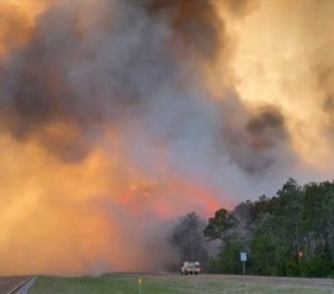In this image made from video taken May 6, 2020 by the Florida Department of Agriculture and Consumer Services, fire and smoke rise from trees alongside a road in Santa Rosa County, Florida. Wildfires raging in the Florida Panhandle have forced nearly 500 people to evacuate from their homes, authorities said. (Photo/Florida Department of Agriculture and Consumer Services via AP)