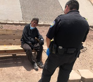 Gallup Police Officer J. Soseeah, right, checks on the health of a homeless woman in Gallup, N.M., Thursday, April 7, 2020. (AP Photo/Morgan Lee)