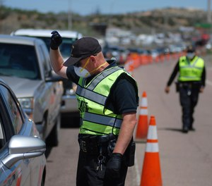 New Mexico state police officers screen cars for compliance with an emergency lockdown order that bans nonessential visitors and limits vehicle passengers to two people as they enter Gallup, N.M., Thursday, May 7, 2020.