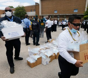 Volunteer firefighters load boxes of personal protective equipment during a health equity community event Tuesday May 12, 2020, in Richmond, Va. (AP Photo/Steve Helber)