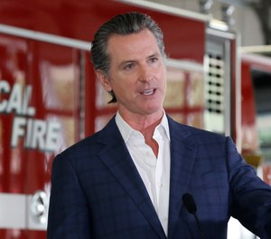 In this May 13, 2020 photo, California Gov. Gavin Newsom discusses the state budget during a news conference at the CAL FIRE/Cameron Park Fire Station. California's state firefighters' union has agreed this week to a 7.5% pay cut for state firefighters after negotiations with Newsom's administration.