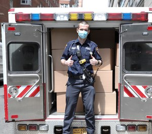 An FDNY EMT loads vehicles during the NYC Healthcare Heroes Aramark event at 435 East 26th Street on Thursday, May 14, 2020 in New York.