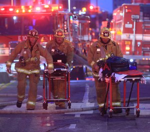 Los Angeles Fire Department firefighters push ambulance cots at the scene of a structure fire that injured multiple firefighters, according to a fire department spokesman, Saturday, May 16, 2020, in Los Angeles.