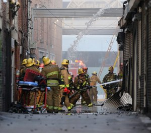Los Angeles Fire Department firefighters work the scene of a structure fire that injured multiple firefighters, according to a fire department spokesman, Saturday, May 16, 2020, in Los Angeles.