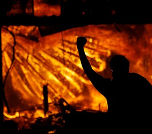A protester gestures in front of the burning 3rd Precinct building of the Minneapolis Police Department on Thursday, May 28, 2020, in Minneapolis.