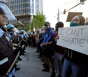 People confront police officers during a protest over the death of George Floyd in Chicago, Saturday, May 30, 2020.
