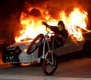 A protester on a bicycle rides past a burning police car during a protest next to the city of Miami Police Department, Saturday, May 30, 2020, downtown in Miami. (AP Photo/Wilfredo Lee)