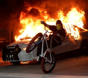 A protester on a bicycle rides past a burning police car during a protest next to the city of Miami Police Department, Saturday, May 30, 2020, downtown in Miami.