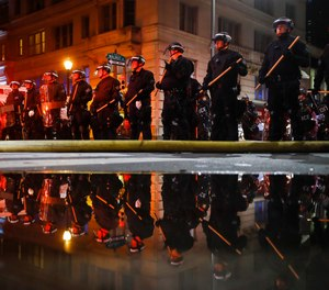 Police are reflected as they stand guard Saturday, May 30, 2020, in Philadelphia, during a protest over the death of George Floyd.(AP Photo/Matt Rourke)
