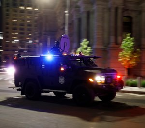 An armored Philadelphia police vehicle drives past City Hall during the Justice for George Floyd Philadelphia Protest, Saturday, May 30, 2020.