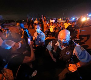 Police officers take a knee alongside protesters who took over the elevated Interstate 10 during a march in New Orleans, Tuesday, June 2, 2020, protesting the death of George Floyd.