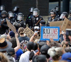 Police officers behind a barricade watch as protesters fill the street in front of Seattle City Hall on Wednesday, June 3, 2020, in Seattle. Seattle City Councilmember Andrew Lewis has introduced legislation that would divert police funds to a program that would dispatch medics and crisis workers to mental health calls.