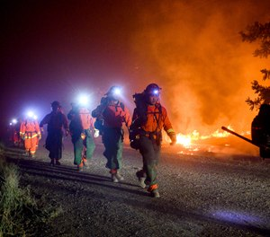 Inmate firefighters, left, battle the Quail Fire burning near Winters, Calif., on Sunday, June 7, 2020. An outbreak at a California prison has caused more than half of the state's inmate firefighting crews to be unavailable to due fire camp lockdowns. (AP Photo/Noah Berger)