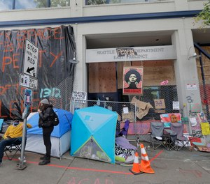 Posters and signs are hung on fencing around the East Precinct building of the Seattle Police Department, Sunday, June 14, 2020, inside what has been named the Capitol Hill Autonomous Zone (CHAZ) in Seattle.