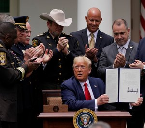 Law enforcement officials applaud after President Donald Trump signed an executive order on police reform, in the Rose Garden of the White House, Tuesday, June 16, 2020, in Washington.