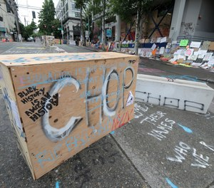 CHOP is spray painted on a barricade, Saturday, June 20, 2020, inside what has been named the Capitol Hill Occupied Protest zone in Seattle. A pre-dawn shooting near the area left one person dead and critically injured another person, authorities said Saturday.