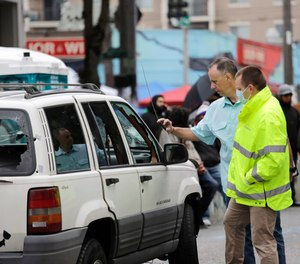 Seattle police investigators look over a car involved in a shooting, Monday, June 29, 2020, in Seattle, where streets are blocked off in what has been named the Capitol Hill Occupied Protest zone. A 16-year-old boy was killed and a 14-year-old boy was wounded in the shooting. (AP Photo/Elaine Thompson)