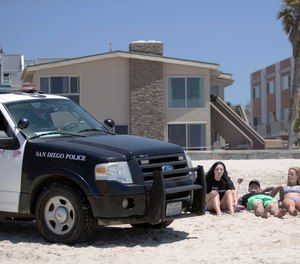 In this May 22, 2020, file photo, San Diego police officers ask three people to get up from the beach, which was closed to sitting or lying down, in San Diego. (AP Photo/Gregory Bull, File)