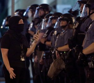 A woman confronts a line of police as protesters gathered at the police headquarters in downtown Kansas City, Mo. Friday, July 17, 2020. Demonstrators were demanding police reforms and an end to Operation Legend, a federal initiative that will deploy 225 federal law enforcement agents to combat crime in the city. (AP Photo/Charlie Riedel)