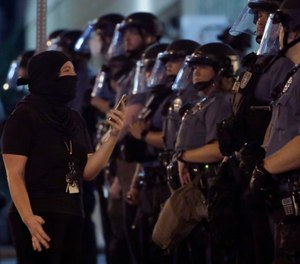 A woman confronts a line of police as protesters gathered at the police headquarters in downtown Kansas City, Mo. Friday, July 17, 2020. Demonstrators were demanding police reforms and an end to Operation Legend, a federal initiative that will deploy 225 federal law enforcement agents to combat crime in the city.