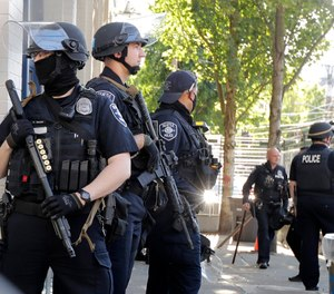 Seattle Police officers stand guard outside the East Precinct Building, Sunday, July 19, 2020 in Seattle. (AP Photo/Ted S. Warren)