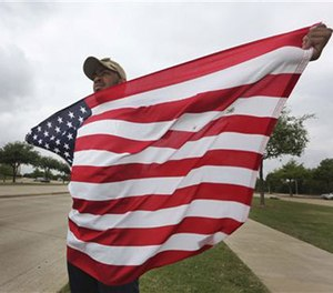 Joseph Offutt, 20, holds a U.S. flag across the street from the Curtis Culwell Center, Tuesday, May 5, 2015, in Garland, Texas.