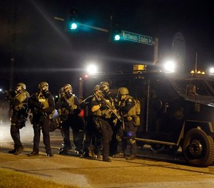 Police take up positions after being shot at Monday, Aug. 18, 2014, in Ferguson, Mo.