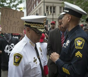 Cincinnati Police Chief Jeffrey Blackwell passes a sign that reads