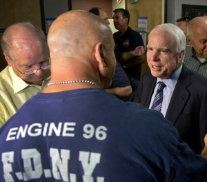 Sen. John McCain speaks with firefighter Thom Yuneman, Friday, July 5, 2013 in Prescott, Ariz. (AP Photo/Julie Jacobson)