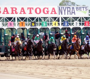 Race fans watch horses break from the starting gate during the first race on opening day of the season at Saratoga Race Course in Saratoga Springs, N.Y., Friday, July 22, 2016. An attorney representing residents has argued against building a $6.6 million fire/EMS station near the track due to zoning issues and concerns it will disturb the horses.