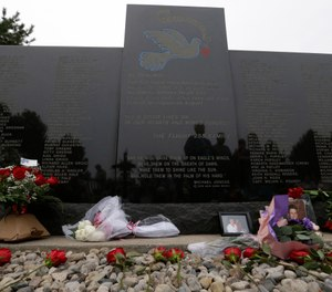 Flowers and pictures are shown at a memorial for the victims of the 1987 Northwest Airlines Flight 255 crash near Detroit Metropolitan Airport. The MD-80 aircraft crashed in the Detroit suburb of Romulus, killing all 154 people aboard except for a 4-year-old girl. Two people also died on the ground. (AP Photo/Paul Sancya)