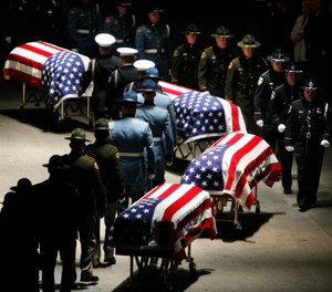 In this Dec. 8, 2009, file photo, police officers approach the caskets of four slain Lakewood police officers as they prepare to fold the flags draped on them during a memorial service at the Tacoma Dome in Tacoma, Wash.