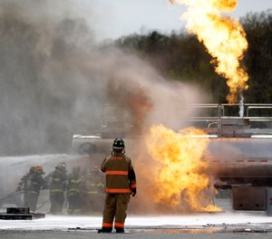 A State Fire instructor watches as firefighters spray fire suppressant foam to douse flames on a tanker truck in a simulated oil-spill fire during a drill.