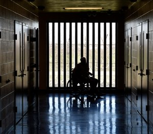 A patient in the medical wing of the Kentucky State Reformatory, looks out the window at the yard Thursday, April 17, 2014, in LaGrange, Ky. (AP Photo/Timothy D. Easley)
